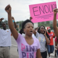 Protesters walk on West Florissant Avenue in Ferguson, Mo., on Tuesday. Protests have been going on for more than a week after the police shooting of unarmed teen Michael Brown.