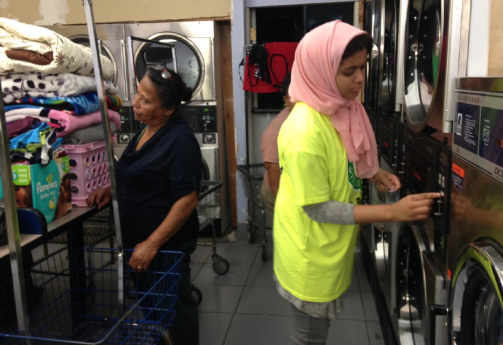 A volunteer with Islamic Circle of North America Relief puts coins into a dryer for Anaheim residents during a free laundry night, sponsored by the Islamic charity group.