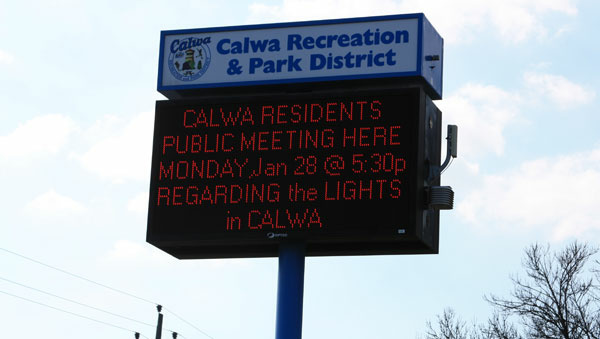 A sign calls for a public meeting on Calwa's streetlights.