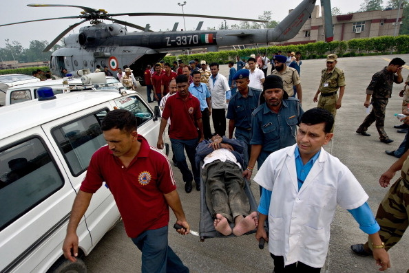 An Indian pilgrim, evacuated from flood-hit areas by the Indian Air Force, is transported on a stretcher by medics at the Jolly Grant Airport in Dehradun, state capital of Uttarakhand on June 21, 2013. Rescue workers recovered scores of bodies from the Ganges river in northern India on June 21, as the death toll from flash floods and landslides topped 500, with thousands of mainly pilgrims and tourists still stranded.  (Photo: MANAN VATSYAYANA/AFP/Getty Images)