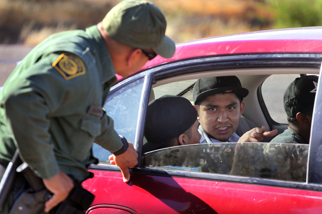 A Border Patrol agent checks vehicles fat a roadside checkpoint June 1, 2010 near Sasabe, Arizona.