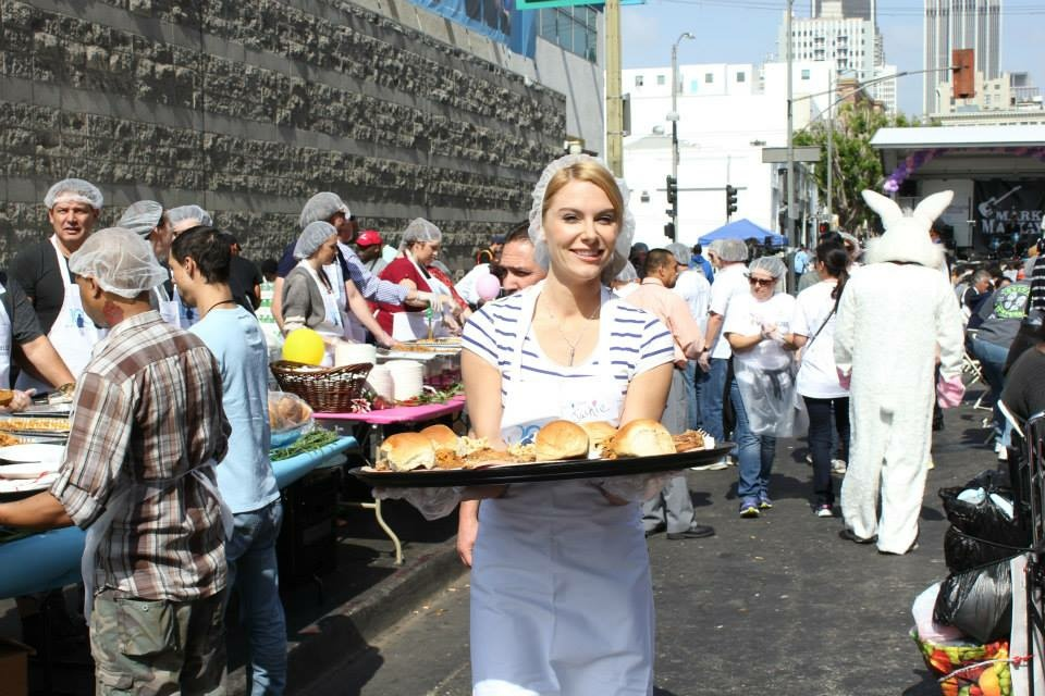 A woman carries meals to guests at the Midnight Mission's Easter Brunch in downtown Los Angeles in 2015.