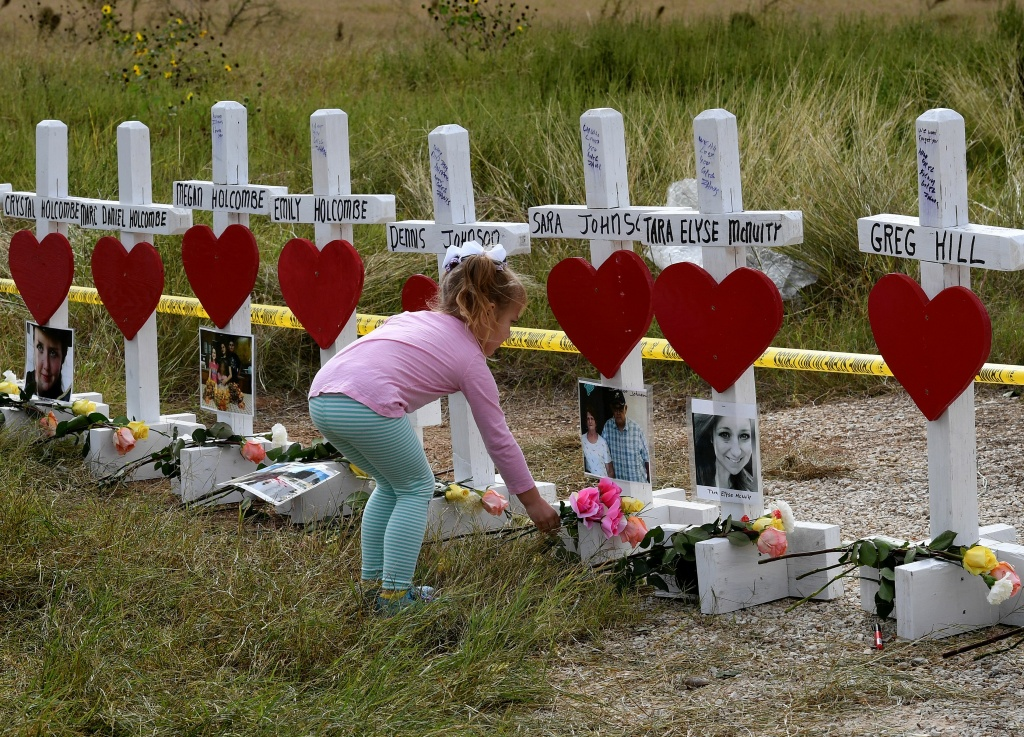 Shaelyn Gisler, 4, leaves flowers at a memorial where 26 crosses were placed to honor the 26 people killed at the First Baptist Church of Sutherland Springs on November 5, 2017 in Sutherland Springs, Texas.