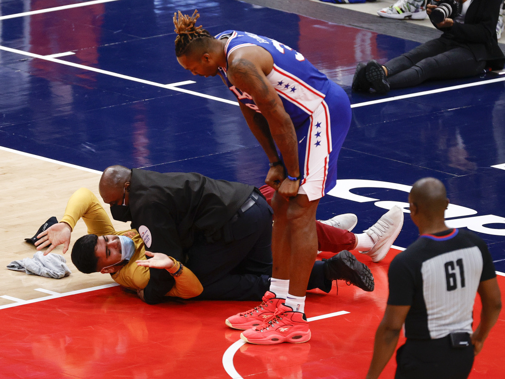 Dwight Howard of the Philadelphia 76ers looks down at a fan who ran onto the court and was tackled by security in Game Four of the Eastern Conference first round series against the Washington Wizards on Monday.
