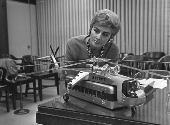 A model of a helicopter with passenger-carrying pod is inspected by Ann Orbeck on April 3, 1965.