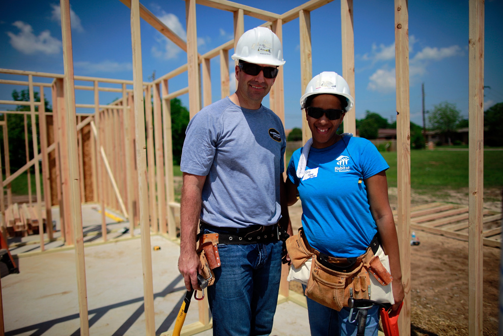 Race car driver Marcos Ambrose (L) works building a home for Tora Barnes (R) with Habitat For Humanity volunteers on April 11, 2012 in Fort Worth, Texas.