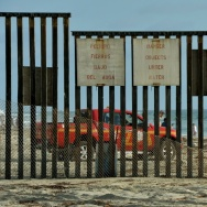 A man looks out towards the US from the Mexican side of the border fence that divides the two countries in San Diego.