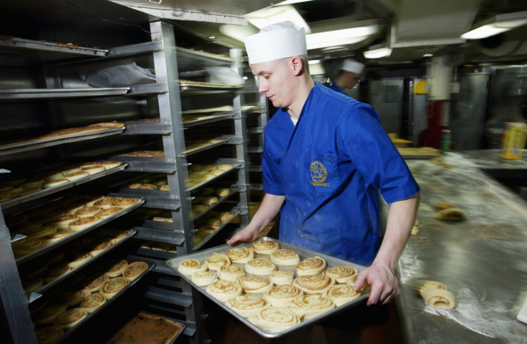 AT SEA - MARCH 8:  MSSN Jerime Jones of Seattle, Washington prepares over 2,400 cinnamon rolls onboard the U.S.S. Constellation March, 8, 2003 in the Arabian Gulf. The U.S.S. Constellation arrived in the Arabian Gulf on December 17, 2002 as part of Operation Enduring Freedom. (Photo by Justin Sullivan/Getty Images)