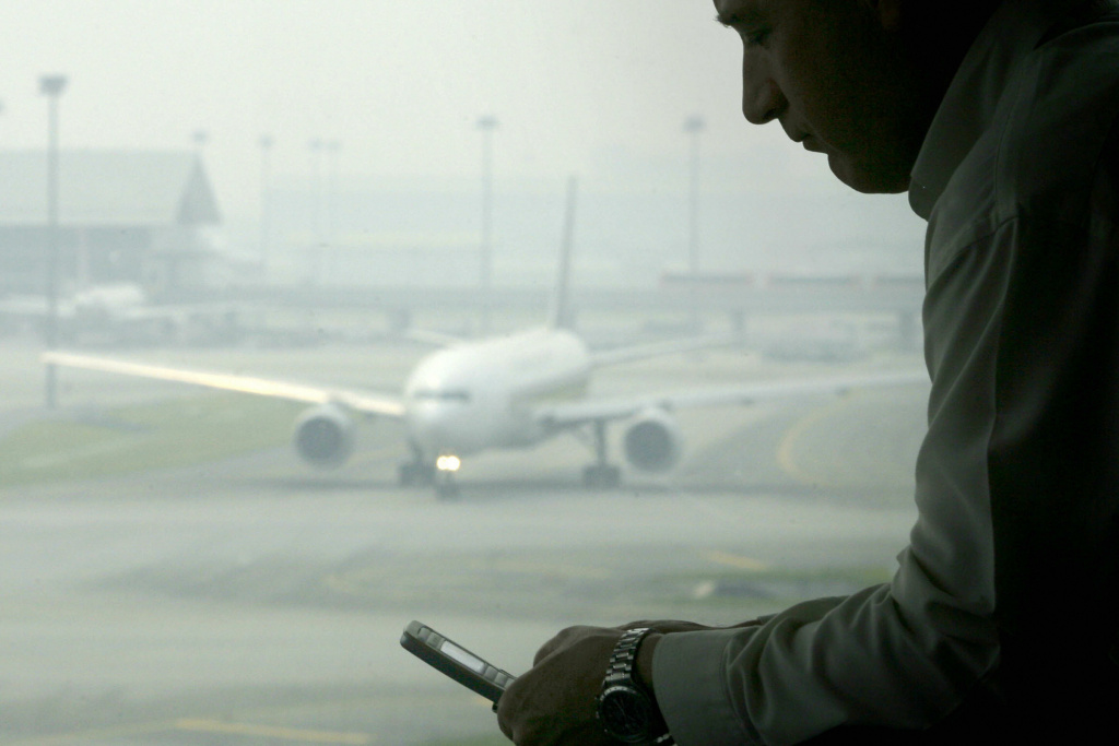 A man reads a text message on his mobile phone while an aircraft taxis at the Kuala Lumpur International Airport.