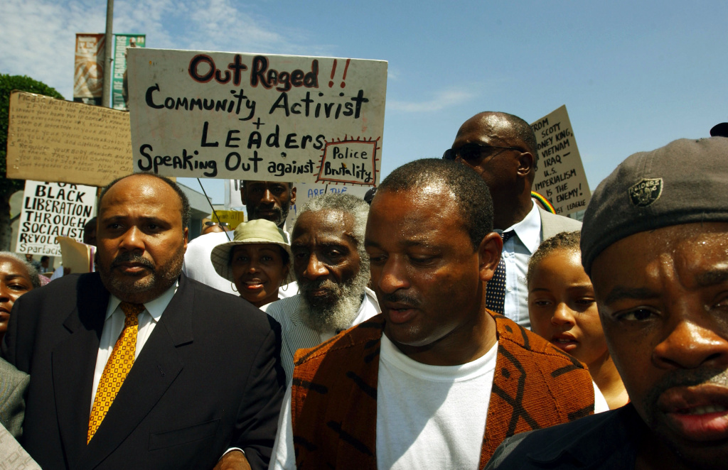 Activists Martin Luther King III (left), Dick Gregory (center) and Najee Ali (right) march to protest the videotaped beating of 16-year-old Donovan Jackson by Inglewood police officers.