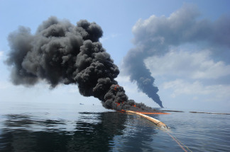 Dark clouds of smoke and fire emerge as oil burns during a controlled fire in the Gulf of Mexico. The U.S. Coast Guard working in partnership with BP PLC, local residents, and other federal agencies conducted the 'in situ burn' to aid in preventing the spread of oil following the April 20 explosion on Mobile Offshore Drilling Unit Deepwater Horizon.