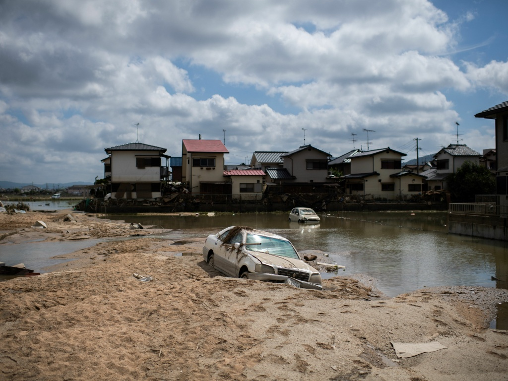 A damaged car is seen stuck in the mud in a flood hit area in Mabi, Okayama prefecture on Tuesday.