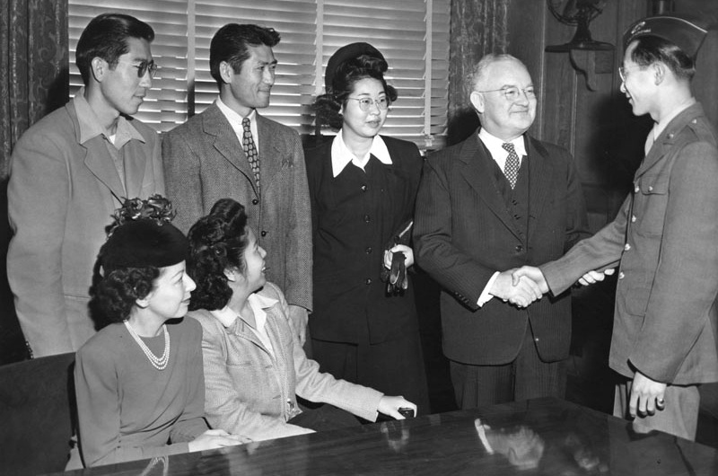 January 15, 1945: Mayor Bowron welcomes Japanese back to LA. L-R: (seated): Mrs. Melba Matsuuro, Mary Yoshimizu; (standing): Jack Yoshimizu, Henry Yoshimizu, Meriko Hoshigama, Mayor Bowron, and Harley M. Oka. Speaking on December 18, 1944, Mayor Bowron said he was fearful that the return of the Japanese might lead to a serious outbreak of race riots and impose a heavy burden on law officers.
