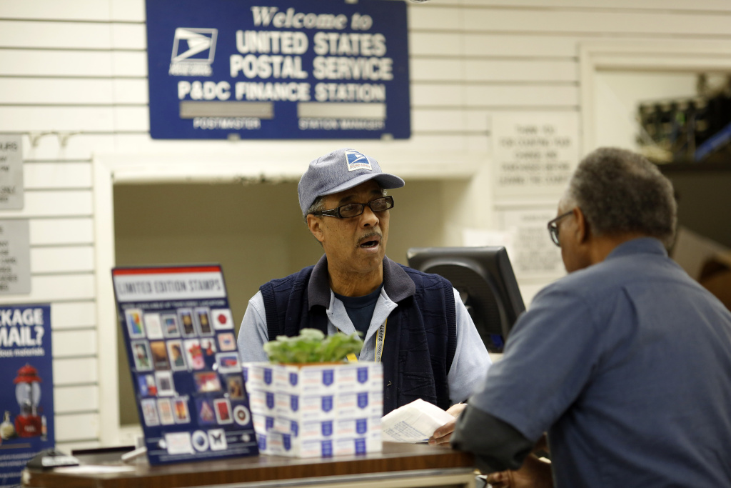 A United States Postal Office employee helps a customer at the post office on Evans Street on December 16, 2013 in San Francisco, California. The U.S. Postal Service lost $2 billion this spring despite increasing its volume and charging consumers more money to send mail, officials said Monday.