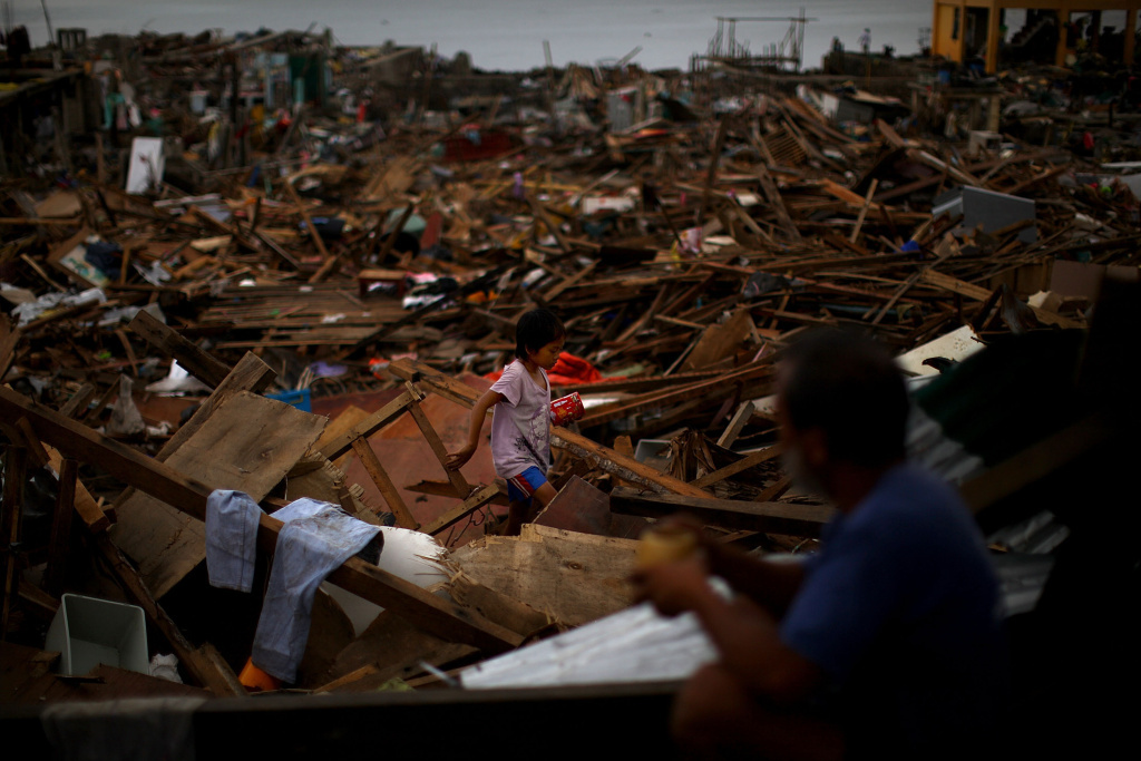 A Filipino girl crosses between collapsed roof tops in the damaged downtown area in Tacloban, Philippines on Sunday.