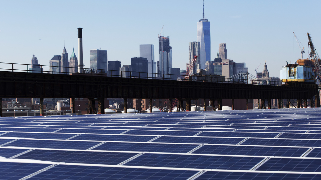 U.S. regulators say cheap solar panels from China have hurt U.S. manufacturers. Here, the Manhattan skyline is seen beyond a rooftop covered with solar panels.