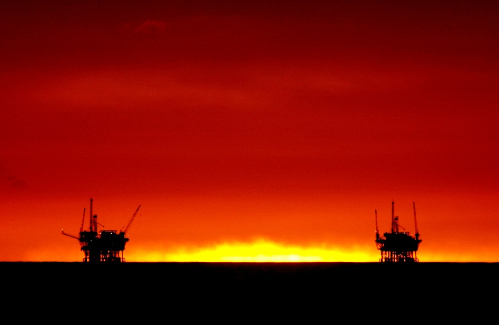 385757 03: The sun fades from view as it sets between the Hillhouse A, left, and Hillhouse B oil and gas platforms near the Federal Ecological Reserve in the Santa Barbara Channel, February 15, 2001, near Santa Barbara, CA.