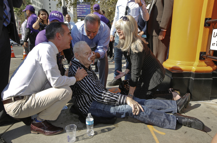 Los Angeles Mayor Eric Garcetti, left, comes to the aid of an unidentified man who collapsed in downtown Los Angeles Thursday, Aug. 31, 2017. The temperature in downtown Los Angeles shot past 90 degrees early in the day and a spectator collapsed just as Mayor Eric Garcetti was about to start a late-morning ceremony to mark the reopening of the city's historic Angels Flight funicular railroad. The man appeared to recover but was taken away by paramedics.
