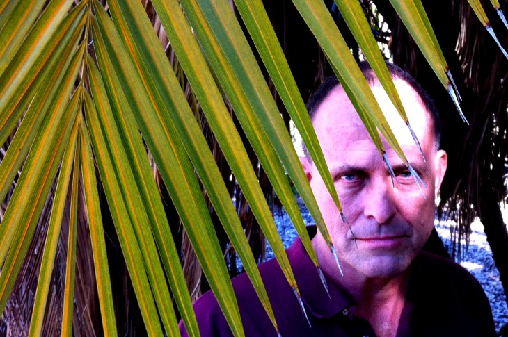 The LA County Arboretum's Frank McDonough peers through the fronds. Instead of the Heart of Darkness, it's the heart of palm.