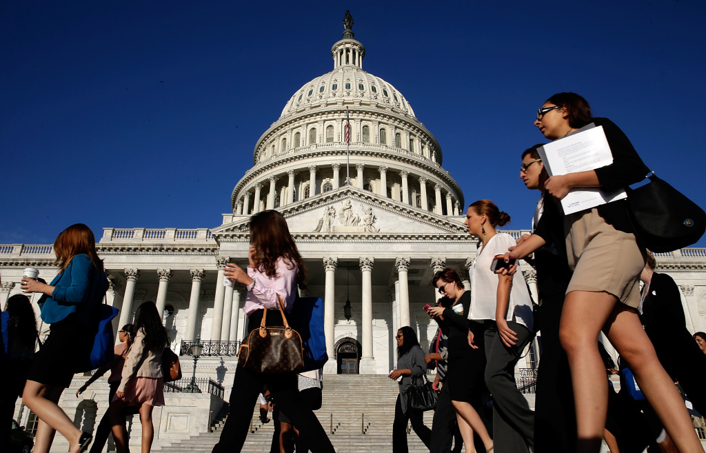 Tourists walk past the U.S. Capitol as the Congress remains gridlocked over legislation to continue funding the federal government