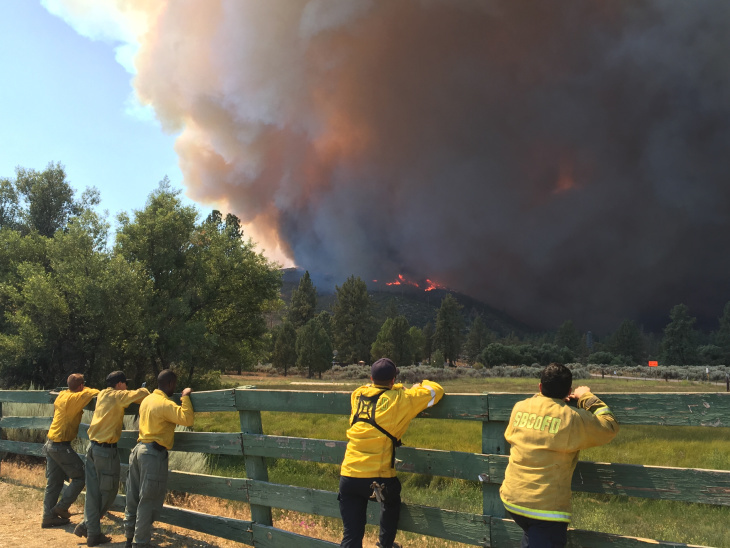 Firefighters watch from the Lake Hemet Campground near the incident command post for the Cranston Fire as flames crawl over Baldy Mountain.