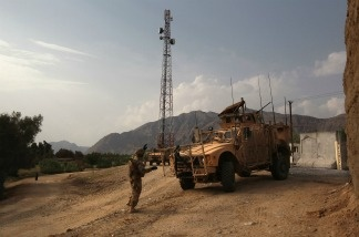 A U.S. Army Mine Resistant Ambush Protected (MRAP) vehicle parks near a cellphone and communications tower.