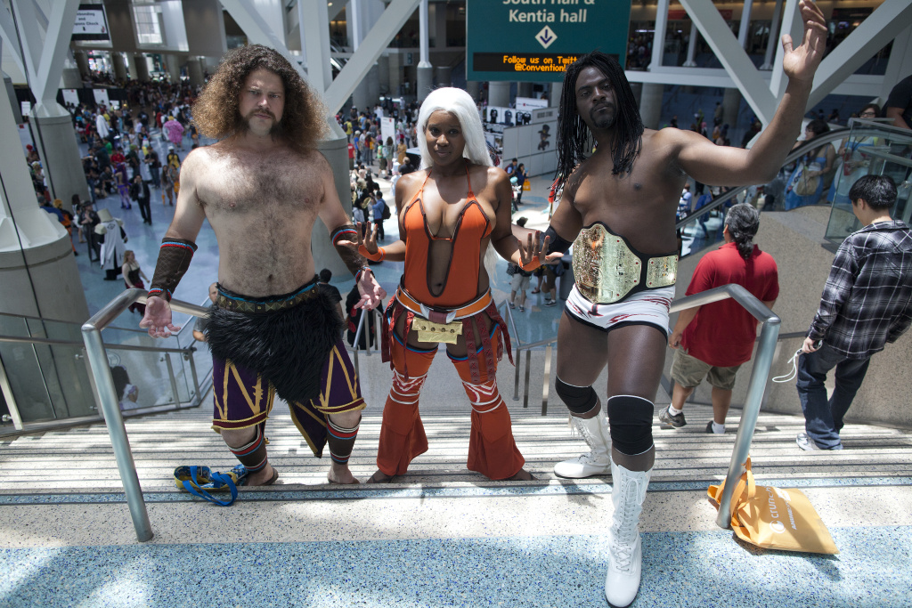 Kevin Booth, left, and Brittney Phillips are dressed as Meng Huo and Zhu Rong from the video game Dynasty Warriors 7 during the Anime Expo at the Los Angeles Convention Center. Aaron Wilson, right, came dressed as the WWE wrestler Booker T.