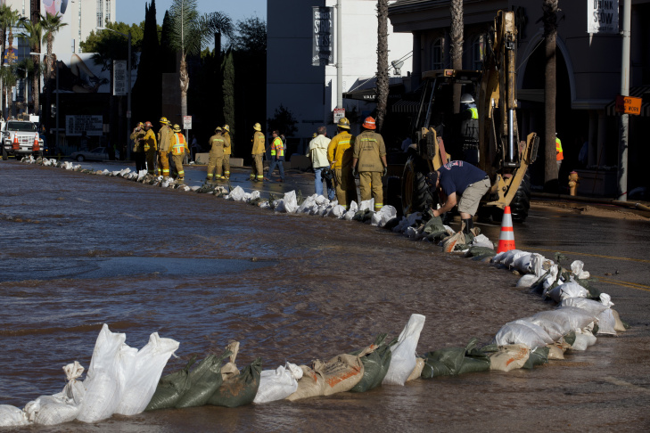 William Lopez shovels water onto the sidewalk to help clear sediment in front of The Grafton on Sunset Boulevard where a water main broke and flooded the street.