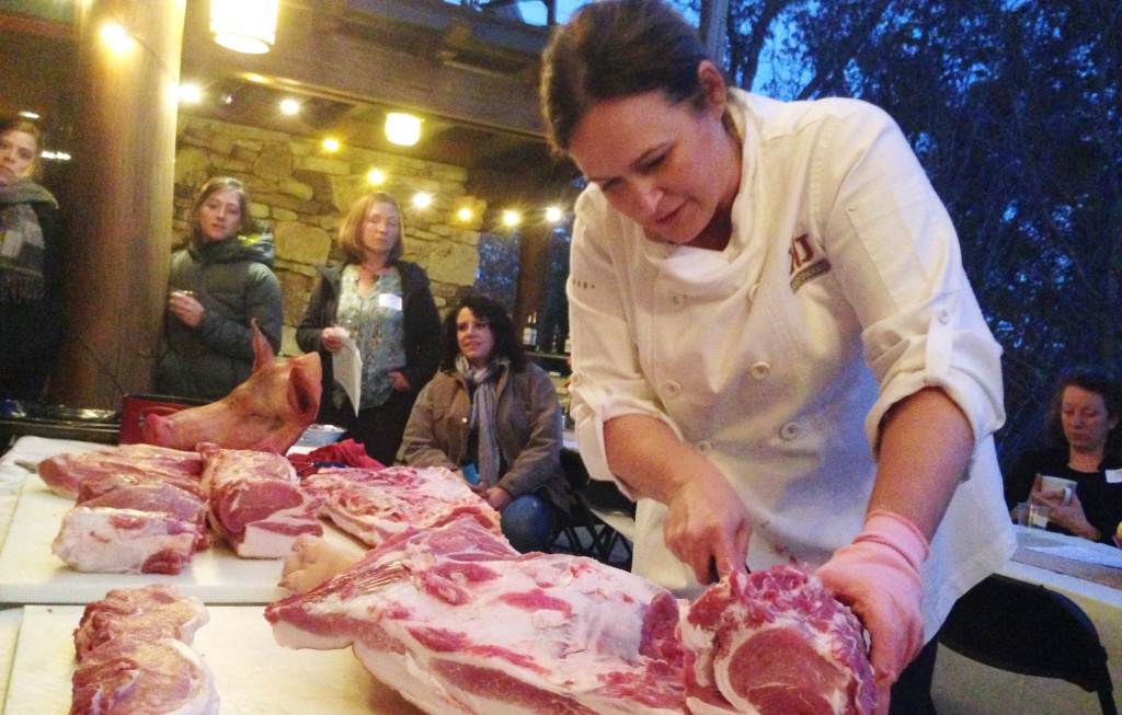 Master butcher Kari Underly cuts into a hog during a