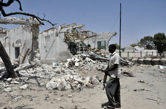 File photo: A government fighter walks by destroyed building after a suicide car bomb ripped through a police base in Mogadishu on February 21, 2011 killing nine people after a weekend of bloody fighting between pro-government forces and Al Qaeda-inspired insurgents.