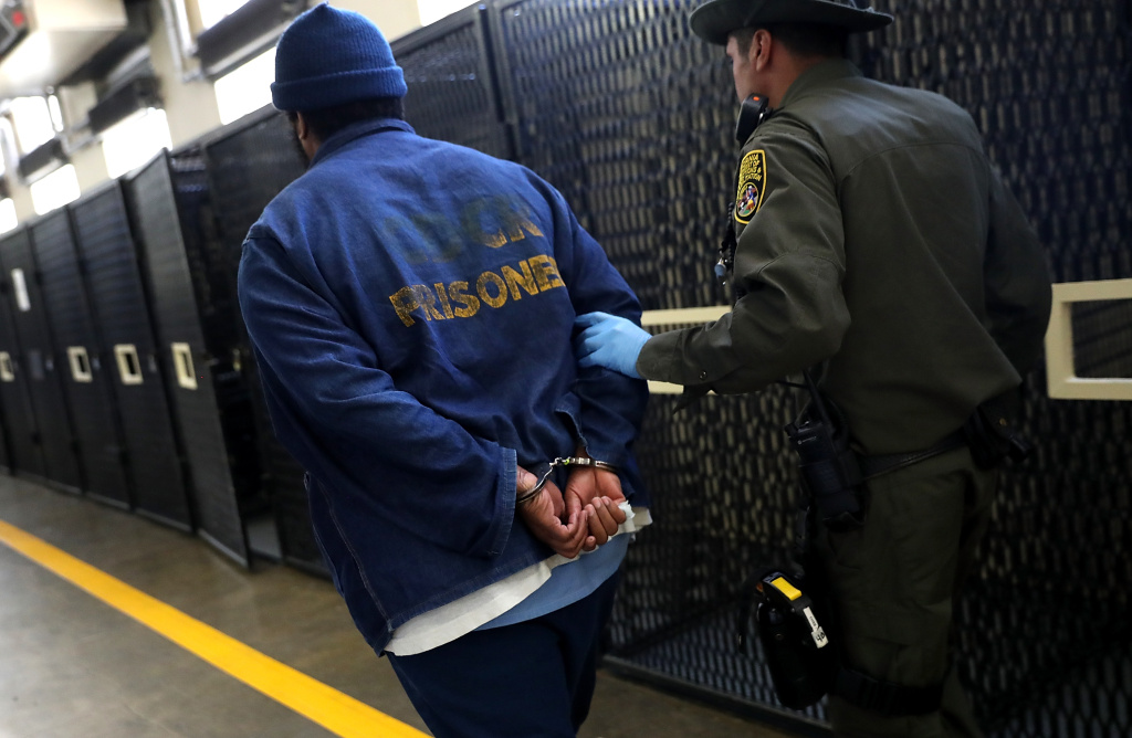 An armed California Department of Corrections and Rehabilitation (CDCR) officer escorts a condemned inamte at San Quentin State Prison's death row on August 15, 2016 in San Quentin, California.
