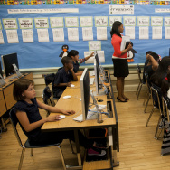 In this photo taken Tuesday, May 15, 2012, Partnership for Los Angeles Coordinator of School Improvement Myeisha Phillips, middle, supervises Ritter Elementary School elementary students practicing their math operator skills in Los Angeles. As teacher layoffs result in larger class sizes, schools are increasingly looking to technology to help bear the load. Some charter schools are investing heavily in classroom computers, and Los Angeles Unified is also exploring the idea.  (AP Photo/Damian Dovarganes)