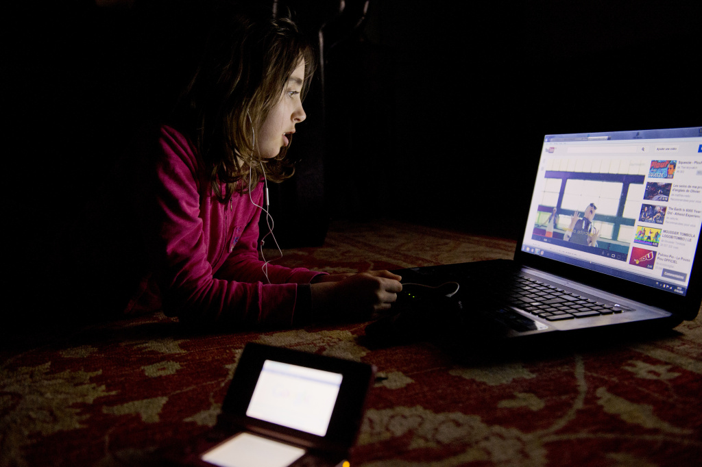 A girl watches a video on youtube on a computer on February 27, 2013 in Chisseaux near Tours, central France.