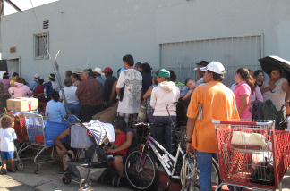 Californians stand in a long line at Helping One Another Progress, a church-run food bank east of downtown Los Angeles. People at the front of the line arrived at 3 a.m. to get a ticket and wait for a single box of groceries.