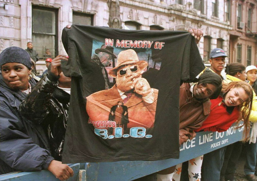 A man displays a T-shirt tribute to rapper Biggie Smalls, aka The Notorious B.I.G., March 18, 1996 as friends and fans lined the funeral procession route through his old neighborhood in Brooklyn.