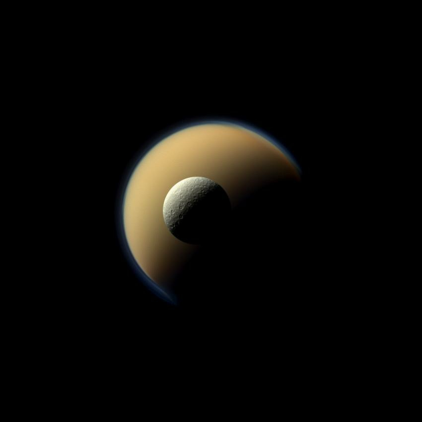 Saturn's largest and second largest moons, Titan and Rhea, appear to be stacked on top of each other in this true-color scene from NASA's Cassini spacecraft. The north polar hood can be seen on Titan (3,200 miles across) appearing as a detached layer at the top of the moon on the top right. Images taken using red, green and blue spectral filters were combined to create this natural-color view. The images were acquired with Cassini's narrow-angle camera on June 16, 2011, at a distance of approximately 1.1 million miles.