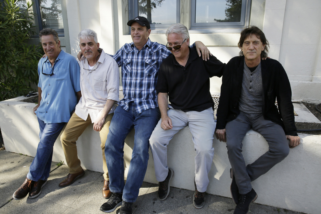 In this Friday, April 13, 2018, photo, the Waldos, from left, Mark Gravitch, Larry Schwartz, Dave Reddix, Jeffrey Noel and Steve Capper sit on a wall they used to frequent at San Rafael High School in San Rafael, Calif.