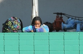 After being released from a school lockdown a student rests her head on a wall outside Gardena High School in Gardena, California January 18, 2011.