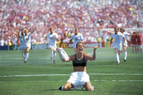 Soccer: World Cup, USA Brandi Chastain victorious after scoring winning penalty kick as teammates celebrate in final vs CHN, Pasadena, CA July 10, 1999.