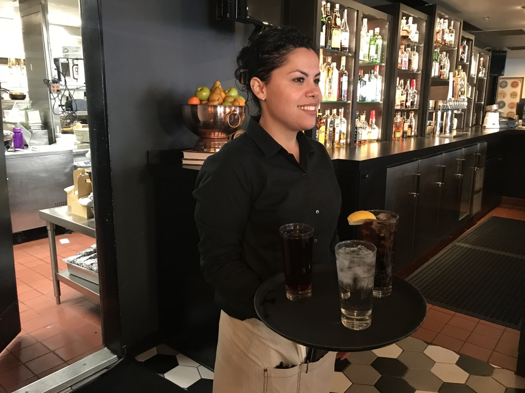 A server carries a tray of drinks to diners at Green Street Restaurant in Pasadena, Feb. 7, 2019 (David Wagner/KPCC).