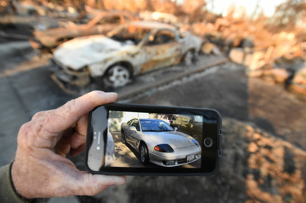 Car collector Gary Dower holds up a photo showing his 1992 Dodge Stealth before it burned at his home in Santa Rosa, California on October 20, 2017.  Residents are being allowed to return to their burned homes on October 20 to grieve and search through remains. Around 5,700 homes and businesses have been destroyed by the fires, the deadliest in California's history. / AFP PHOTO / JOSH EDELSON        (Photo credit should read JOSH EDELSON/AFP/Getty Images)