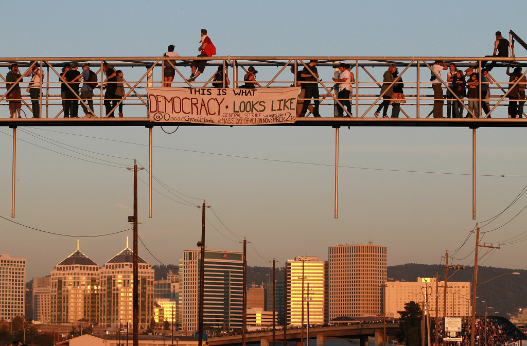 Protesters climb on a railroad crossing at the Port of Oakland during Occupy Oakland's general strike on November 2, 2011 in Oakland, California.