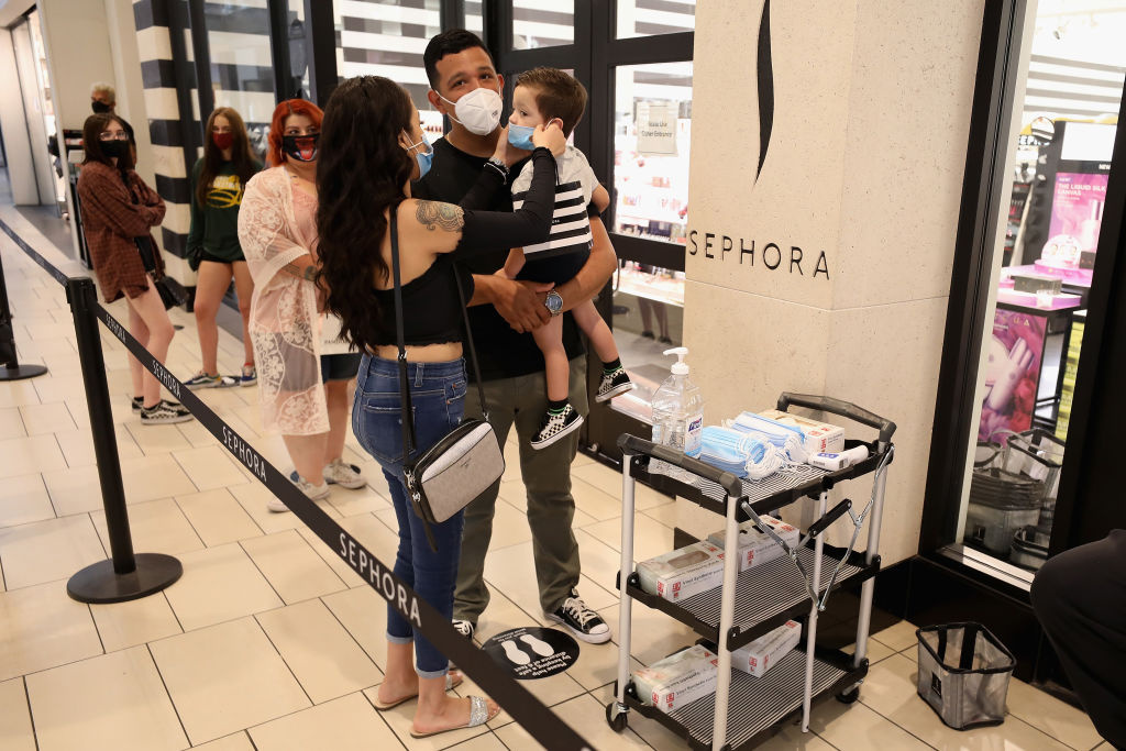 Consumers apply face masks as they stand in line for 'Sephora' at the Arrowhead Towne Center on June 20, 2020 in Glendale, Arizona.