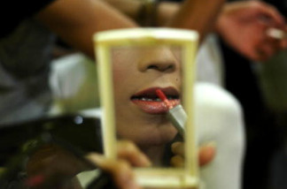 A transgender individual applies makeup after working as a escort in night club to earn money in Yogyakarta, Indonesia.