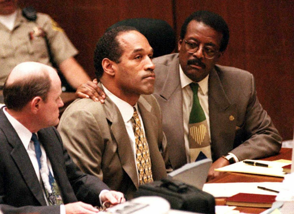 Lead defense attorney Johnnie Cochran (R) puts his arm on O.J. Simpson's (C) shoulder after Simpson told Judge Lance Ito Sept. 22, 1995 in Los Angeles that he has faith that jurors would acquit him of the murder of his ex-wife Nicole Simpson and her friend, Ronald Goldman. At left is defense attorney Robert Blasier (L).