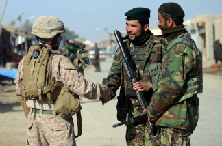 A US Marine of the 2nd Battalion, 1st Marines Regiment (left) shakes hand with Afghanistan National Army soldiers during a patrol in Garmser, Helmand Province, on March 7, 2011.