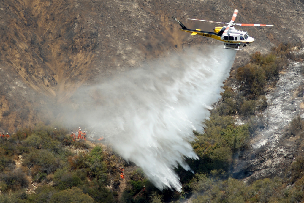 A Los Angeles County Fire Department helicopter drops water near an inmate hand crew cutting a containment line on a ridge at the Williams fire in the Angeles National Forest on September 4, 2012 north of Glendora, California. The fire began late September 2, putting an early end to Labor Day weekend camping and hiking for vacationers, who were evacuated from the area as it spread to more than 4,000 acres in size. Officials project that it will take at least another week to establish a containment line around the fire which is burning in rugged and difficult to reach backcountry.