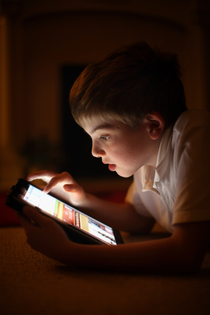 A ten-year-old boy uses an Apple iPad tablet computer in Knutsford, United Kingdom.