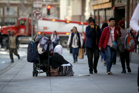 A homeless woman begs for change as pedestrians walk by in San Francisco, California.