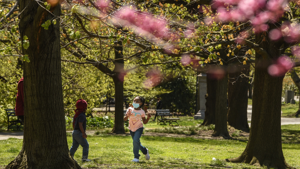 A child wears a protective mask while playing in April in Prospect Park in the Brooklyn borough of New York City.